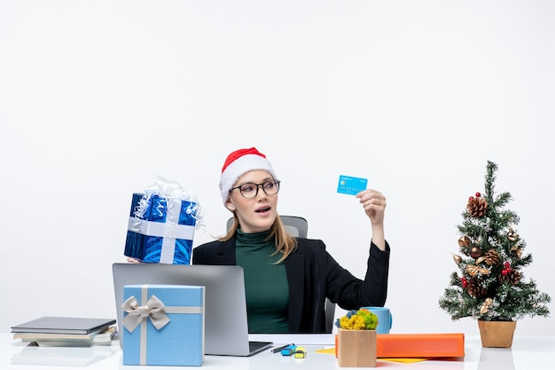 Positive excited business woman with santa claus hat and wearing eyeglasses sitting at a table holding christmas gift and bank card on white background Free Photo