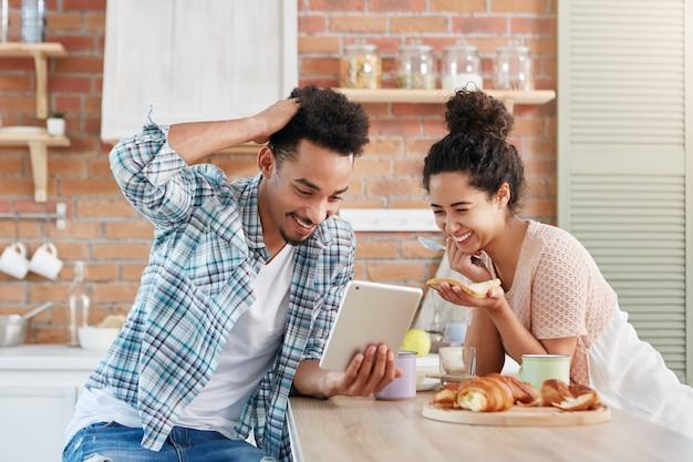 La coppia familiare positiva sorride ampiamente mentre guarda la commedia sul tablet, usa la connessione internet gratuita a casa, Foto Gratuite