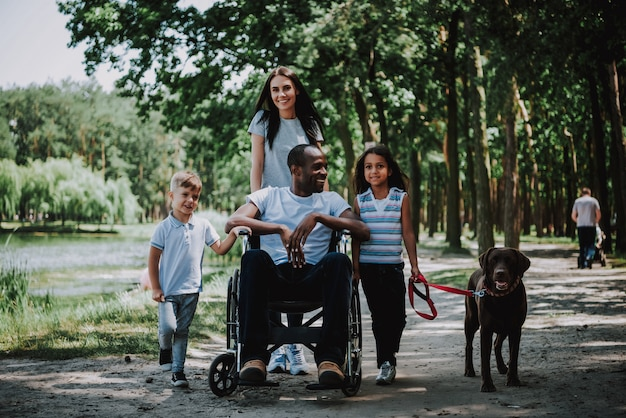 Positive family in park man in wheelchair smiling. Premium Photo