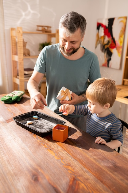 Positive father and son putting cookies into gift box Premium Photo