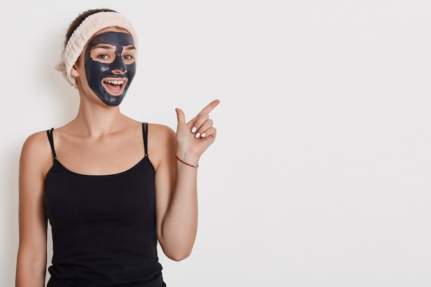 Positive female applies nourishing mask on face, pointing fore finger aside on copy space, undergoes beauty treatments, poses indoor against white wall. copy space. Free Photo