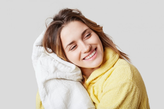 Positive female in bathrobe, holds white towel, rests after taking showr alone, has cheerful expression Free Photo