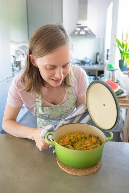 肯定的な女性のブロガーが彼女のキッチンで料理をし、鍋を開いて野菜の食事でチェックしています。垂直ショット。フードブロガーのコンセプト 無料写真