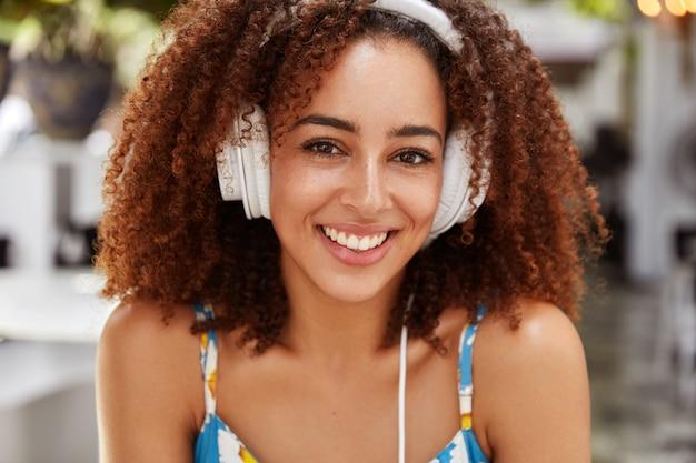 黒い肌とアフロのヘアスタイルを持つ肯定的な女性ブロガーは、携帯電話に接続されて、お気に入りの音楽を聴いている間に屋外を再現します 無料写真