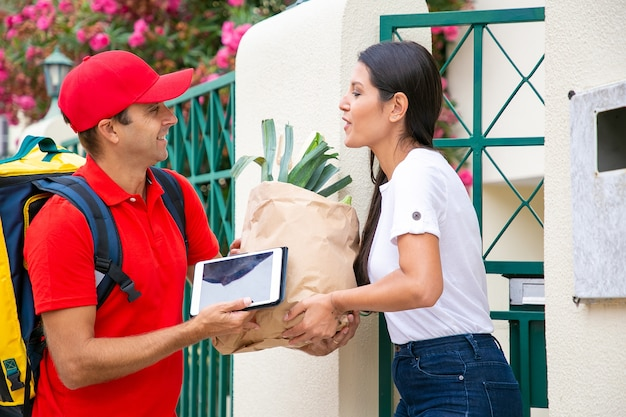 Positive female customer  receiving food from grocery store, taking package from courier at her gate. shipping or delivery service concept Free Photo