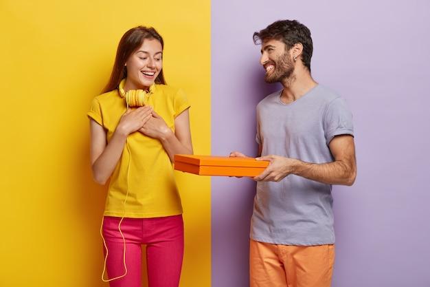 ポジティブな女性は彼氏からプレゼントをもらったことに感謝を感じ、良い感情を表現します。思いやりのある男は彼のガールフレンドに驚きの段ボール箱を与え、誕生日を祝うために来る 無料写真