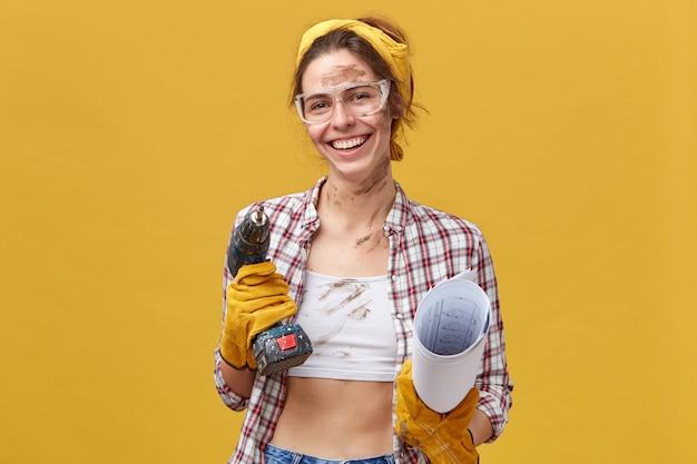 더러운 옷을 드릴과 노란색 벽 위에 절연 된 종이를 들고 그녀의 작업을 완료하는 것을 기쁘게 생각하는 긍정적 인 여성 유지 보수 노동자. 일을 고칠 보호 착용에 여자 무료 사진