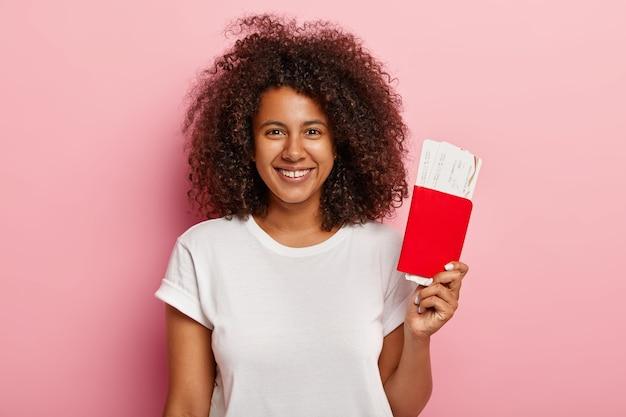 긍정적 인 여성 승객은 탑승권과 여권을 소지하고, 항공 여행을 준비하고, 여행을 즐기고, 곱슬 머리를하고, 흰색 티셔츠를 입고, 완벽한 이빨로 넓게 미소를지었습니다. 무료 사진