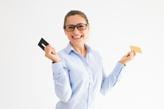 Positive female shopper holding several loyalty cards Free Photo