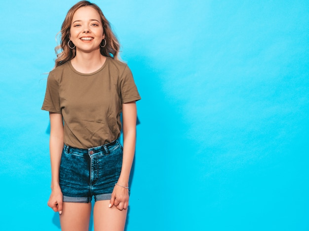 Positive female smiling. funny model posing near blue wall in studio Free Photo