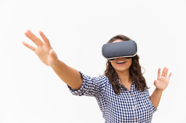 Positive female user in vr goggles touching air and smiling Free Photo