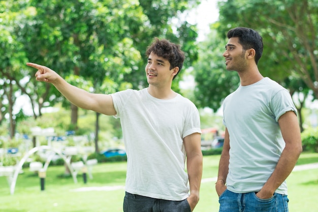 Positive friendly guy showing direction to indian man Free Photo
