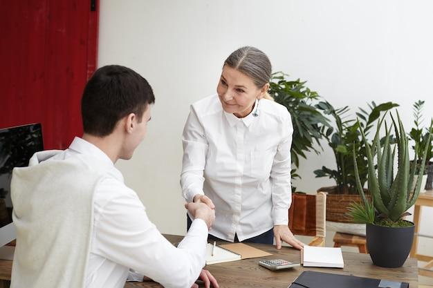 Позитивно выглядящая зрелая женщина-специалист по персоналу стоит за своим офисным столом и пожимает руку неузнаваемому кандидату-мужчине после успешного собеседования. подбор персонала и человеческие ресурсы Бесплатные Фотографии