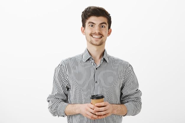 Позитивно-дружелюбный зрелый мужчина с усами и бородой в полосатой рубашке, держит чашку чая или кофе и радостно улыбается, встречает новых людей в офисе, небрежно и беззаботно разговаривает над серой стеной Бесплатные Фотографии
