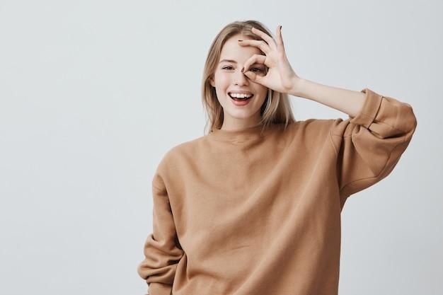 カジュアルな服で肯定的な面白いブロンドの女性はokの標識を示しています 無料写真