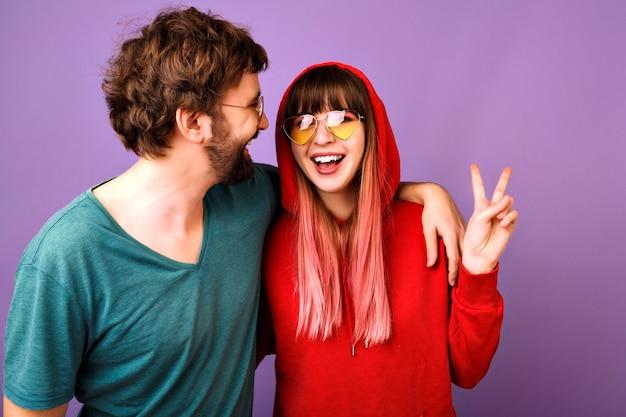 一緒に楽しんでいる幸せなカップル、抱擁と笑い、家族と愛、カジュアルな若者の服とアクセサリー、平和のジェスチャー、紫の壁、関係を示すポジティブな面白い肖像画 無料写真