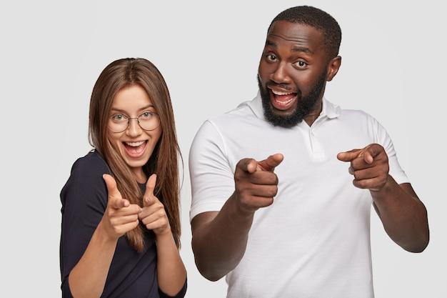 긍정적 인 소녀와 다른 인종의 남자는 손가락 총 제스처를 만들고 긍정적으로 웃으며 선택을 표현합니다. 무료 사진