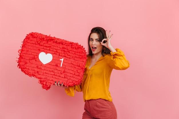 La ragazza positiva in camicetta e pantaloni luminosi tiene come da intagram sulla parete rosa e mostra il segno ok. Foto Gratuite