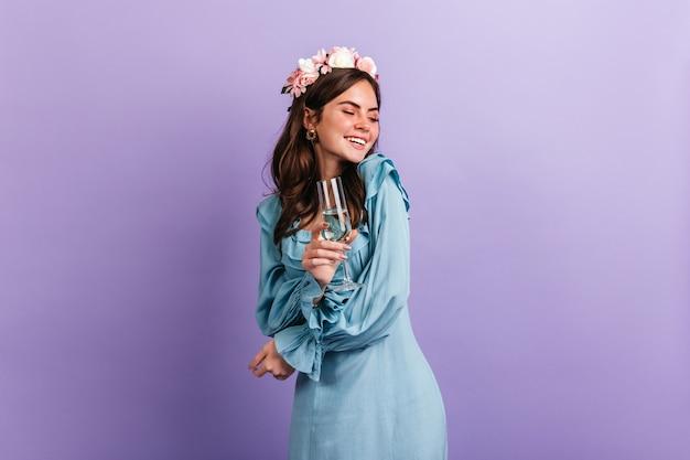 보라색 벽에 파티를 즐기면서 기분이 좋은 긍정적 인 소녀가 웃는다. 샴페인 잔을 들고 파란색 옷 모델. 무료 사진