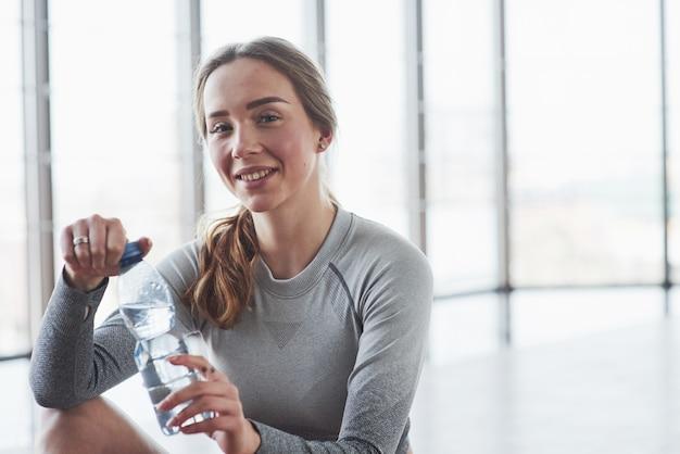 Позитивная девушка отдыхает. спортивная молодая женщина имеет фитнес-день в тренажерном зале в утреннее время Бесплатные Фотографии