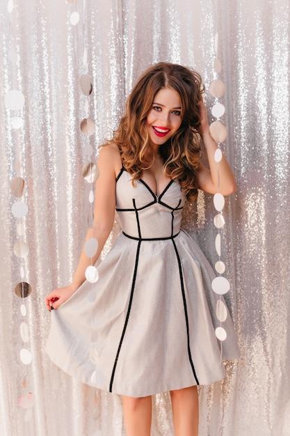 Позитивная девушка с вьющимися волосами в стильном праздничном платье позирует на вечеринке на яркой сияющей стене. Бесплатные Фотографии