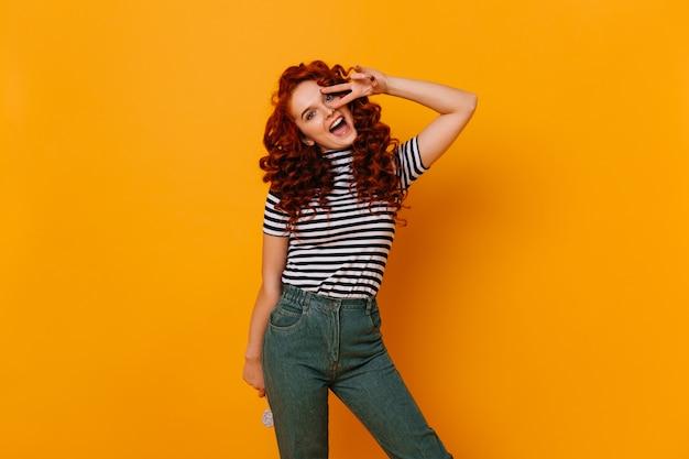 롤리팝을 들고 감정적으로 카메라를보고, 평화 기호를 보여주는 물결 모양의 빨간 머리를 가진 긍정적 인 소녀. 무료 사진