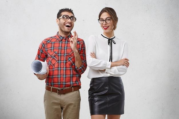 コミカルな表情のポジティブな嬉しい男性が指を交差させ続け、自信に満ちた表情の美しい女性を嬉しそうに見る 無料写真