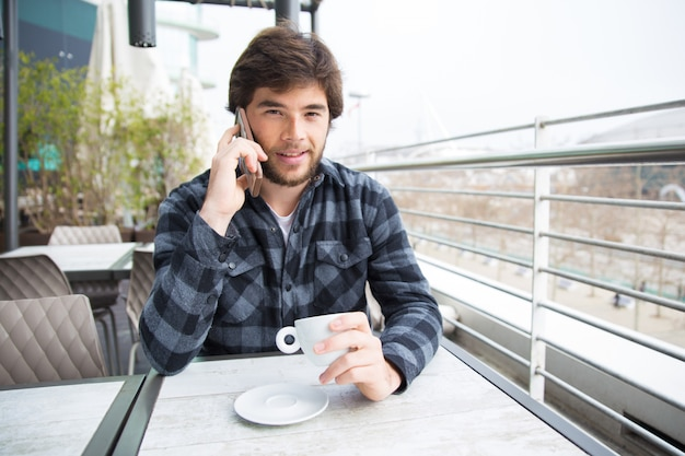 Positive guy enjoying coffee and nice phone talk Free Photo