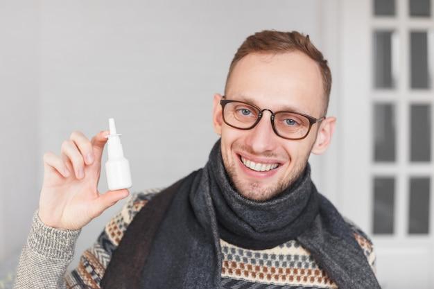 Positive guy showing nasal or eye spray Premium Photo
