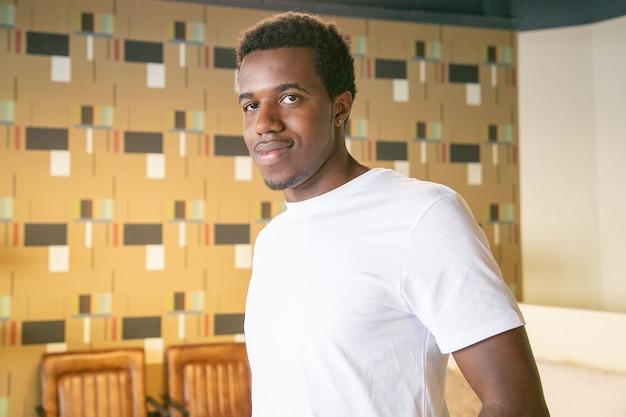 오순절 티셔츠에 긍정적 인 잘 생긴 아프리카 계 미국인 남자가 서서 공동 작업이나 커피 숍 인테리어에서 포즈를 취하고 카메라를보고 무료 사진