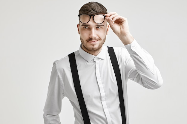 Positive handsome young caucasian man with stubble and stylish haircut looking away with confident flirtatious smile, dressed in white elegant shirt with suspenders, holding his trendy eyeglasses Free Photo