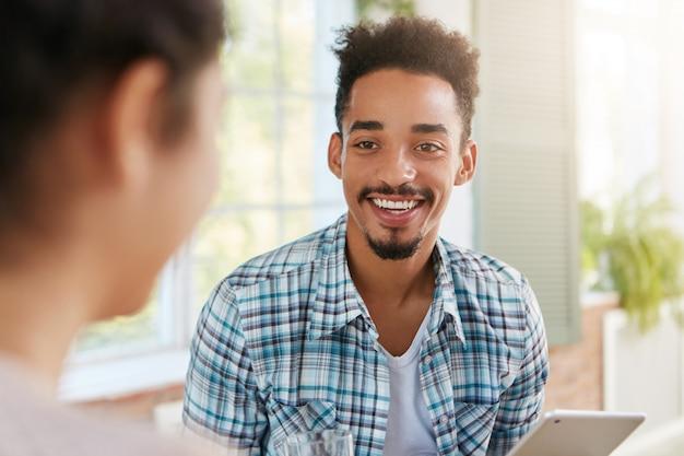 肯定的な幸せな暗い肌の男はひげと口ひげを持っています、広く笑って、白い歯を示しています、 無料写真