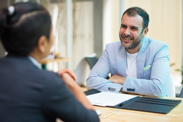 Positive hispanic businessman listening to colleague Free Photo