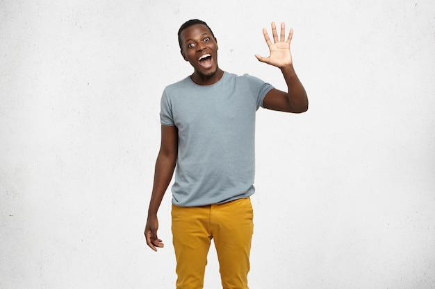 Positive human emotions, facial expressions, feelings, attitude and reaction. friendly-looking polite young african american man dressed in grey t-shirt and mustard jeans saying hi, waving his hand Free Photo