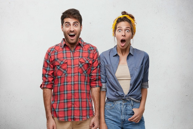 Positive human emotions, feelings, attitude and reaction concept. portrait of surprised young bearded man in red plaid shirt and woman with headband posing Free Photo