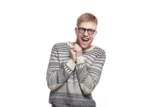 Положительные человеческие эмоции, чувства, реакция и отношение. изображение смешного восторженного студента в очках, держащего сжатые кулаки на груди и широко улыбающегося, взволнованного результатами экзаменов Бесплатные Фотографии