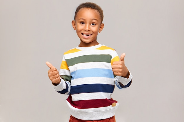Emozioni umane positive, reazioni e sentimenti. ragazzo dalla pelle scura felice emotivo in maglione multicolore che fa i pollici sul gesto, esprimendo accordo, approvazione, dando il suo simile, sorridendo ampiamente Foto Gratuite