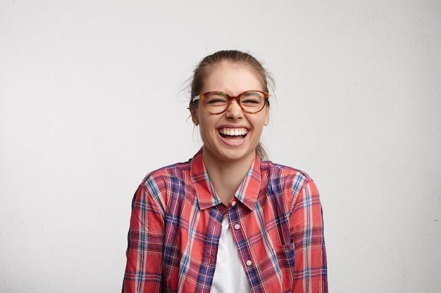 Emozioni umane positive. ritratto in studio di rilassata spensierata giovane donna con sorriso a trentadue denti che indossa occhiali chiudendo gli occhi stretti mentre si ride ad alta voce a buone battute, divertirsi con gli amici in ambienti interni Foto Gratuite