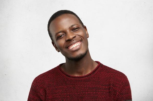 肯定的な人間の表情と感情。カジュアルなセーターに身を包んだハンサムな幸せな浅黒い肌の男の顔写真 無料写真
