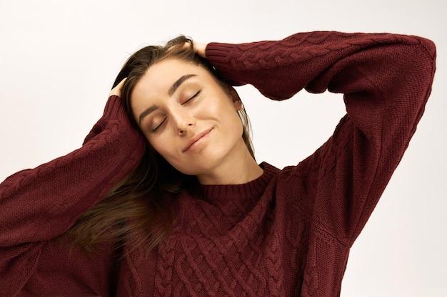 Espressioni facciali umane positive ed emozioni. colpo isolato di affascinante giovane femmina caucasica in maglione lavorato a maglia mantenendo gli occhi chiusi con divertimento, massaggiando la testa e sorridendo con gioia Foto Gratuite
