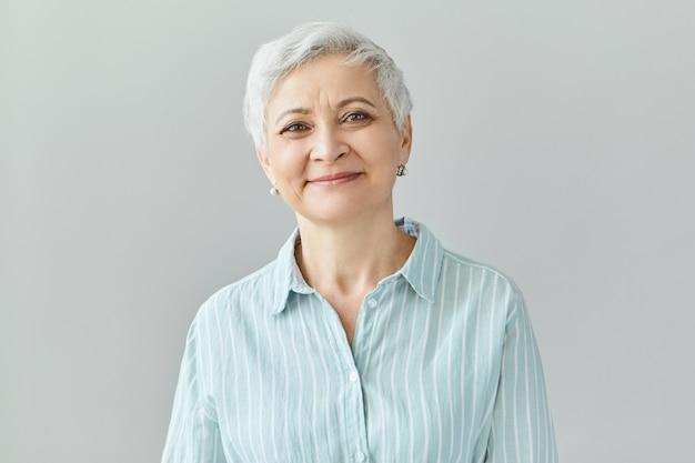 Reazioni umane positive, sentimenti ed emozioni. affascinante ed elegante donna di mezza età di sessant'anni con corti capelli grigi con un sorriso compiaciuto, gli occhi pieni di felicità e gioia Foto Gratuite