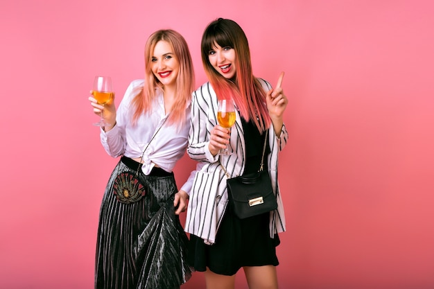 Ritratto positivo dell'interno di due donne graziose eleganti alla moda che si divertono alla festa, bevono champagne gustoso e ballano, abiti da sera da cocktail e muro rosa Foto Gratuite