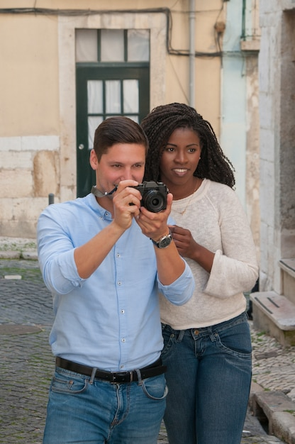 Positive interracial couple taking photos on camera in street Free Photo