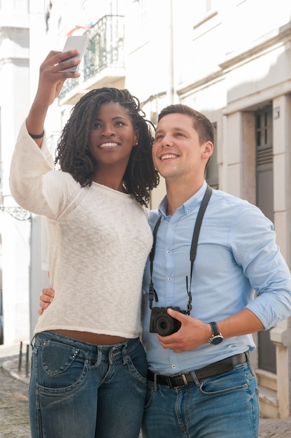 Positive interracial couple taking selfie photo outdoors Free Photo