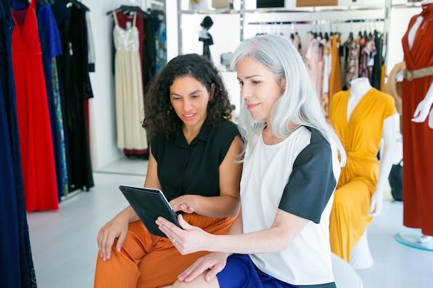 Позитивные дамы сидят вместе и используют планшет, обсуждают одежду и покупки в магазине модной одежды. потребительство или концепция покупок Бесплатные Фотографии