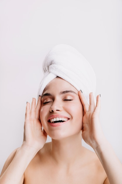 Positive lady enjoys morning spa treatment. girl after shower posing on isolated wall. Free Photo