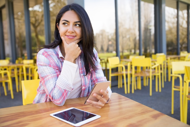 Positive lady using tablet and smartphone in outdoor cafe Free Photo