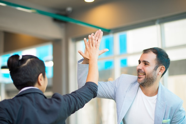 Positive latin and asian managers high fiving Free Photo