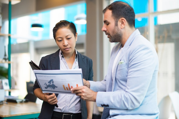 Positive latin man showing report to asian woman with folder Free Photo
