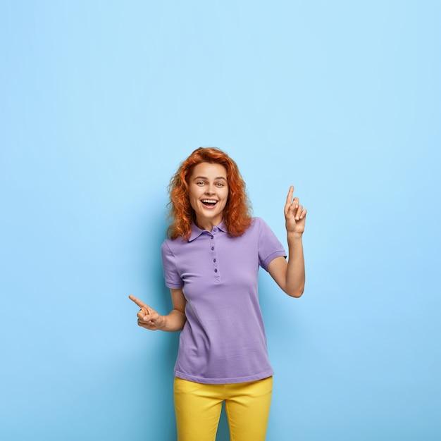 La signora felice dai capelli rossi adorabile positiva indica lateralmente, dà una raccomandazione fantastica Foto Gratuite